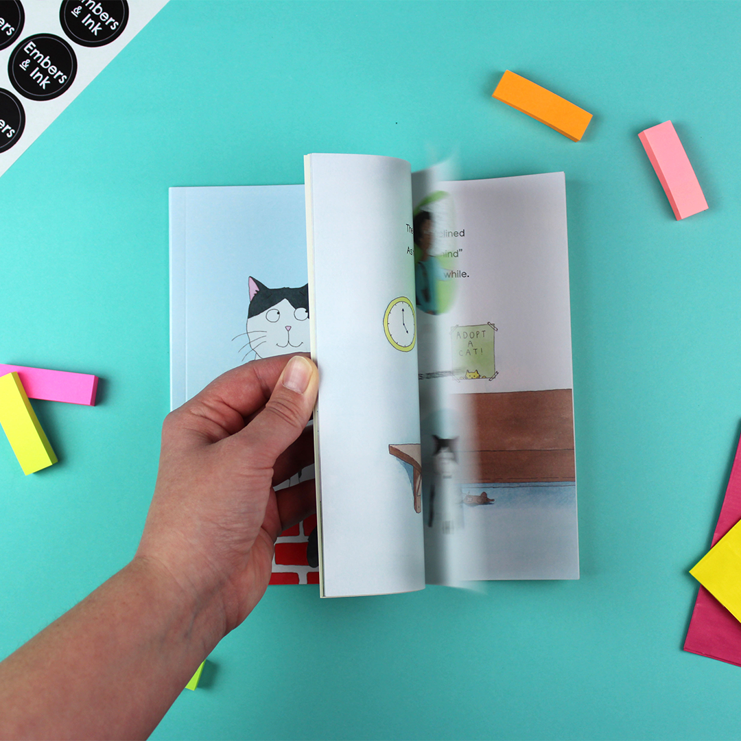 A hand flicks through the pages of Our Dave to show the illustrated pages inside.