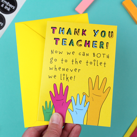 A hand holds a yellow greetings card and yellow envelope. The card has an illustration of raised hands in various colours. The text reads 'thank you teacher, now we can BOTH go to the toilet whenever we like'