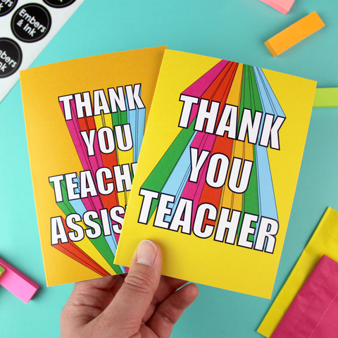 A hand holds two cards, one yellow and one orange. Both have rainbow block letteringg, wth one reading 'thank you teacher' and the other reading'thank you teaching assistant'