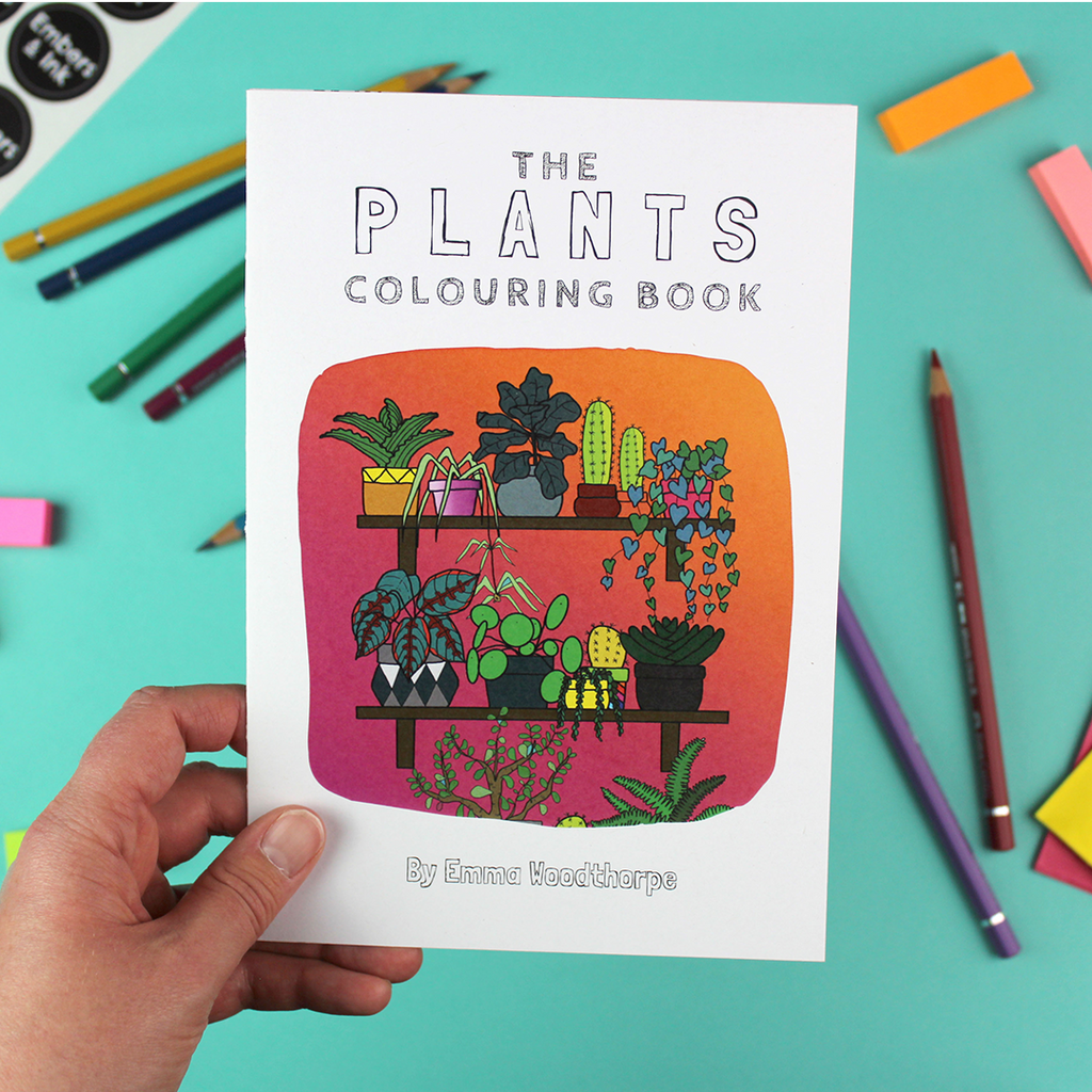 A hand holds up the plants colouring book that has a brightly coloured ilustration of two shelves full of house plants