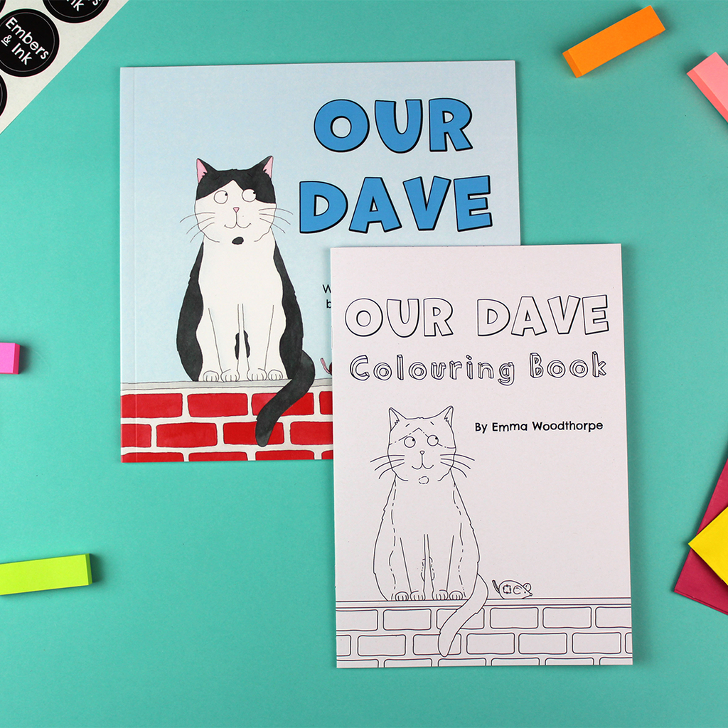 on a table lays the Our Dave rhyming children's picture book and the Our Dave colouring Book. Both covers show a cat sitting on a wall next to a toy mouse. The children's book is coloured blue, red, black and white and the colouring book is black and white