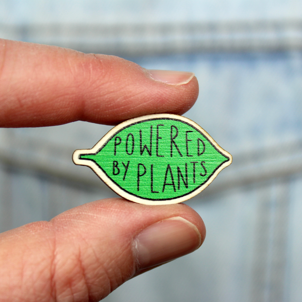 A wooden pin badge in the shape of a green leaf contains the words Powered by Plants. The badge is held between finger and thumb in front of a denim jacket pocket.