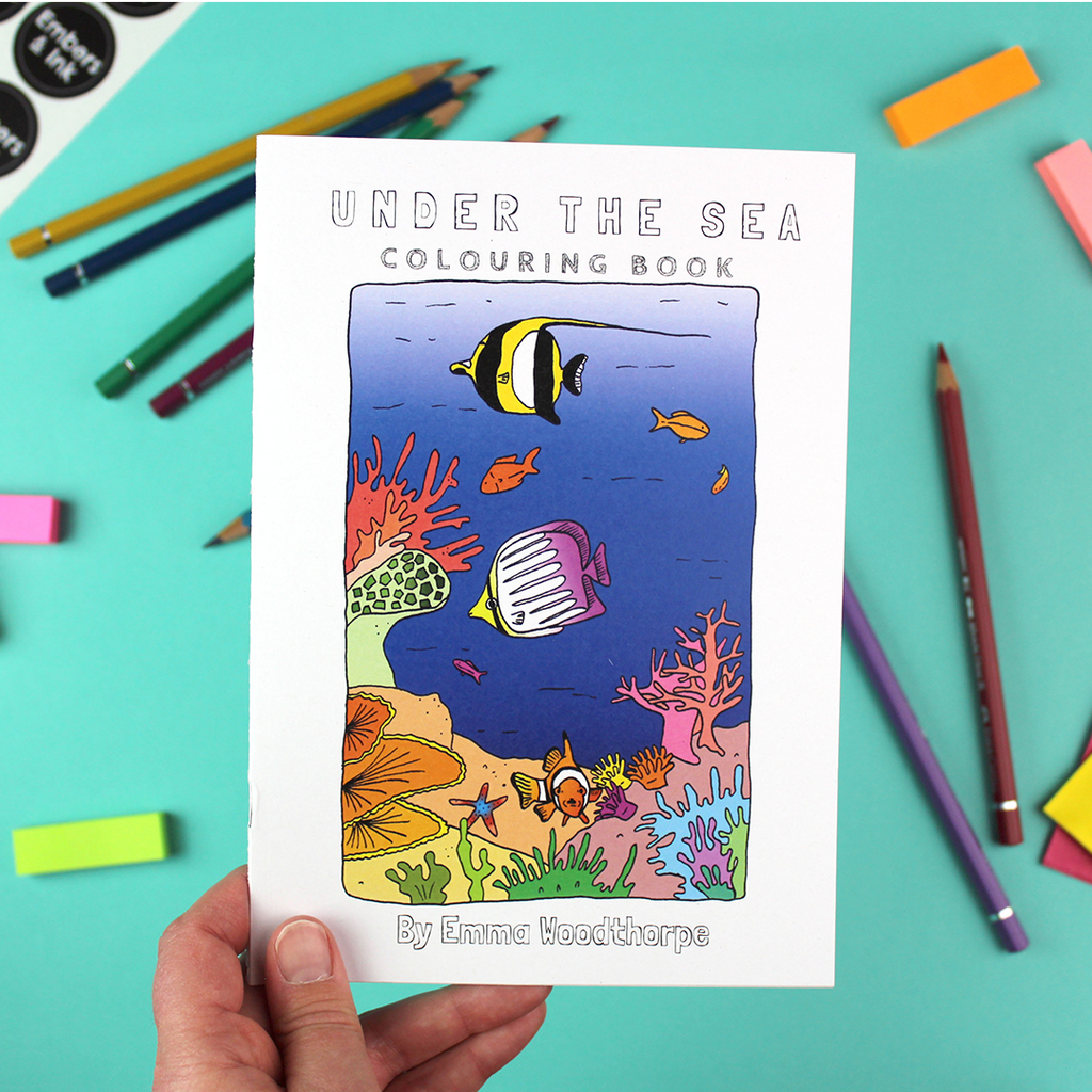 A hand holds the Under the Sea colouring book. the front cover has an illustration of a colourful coral-reef scene.