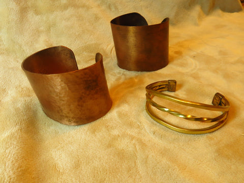 2 wide copper cuffs and one triple wire brass cuff