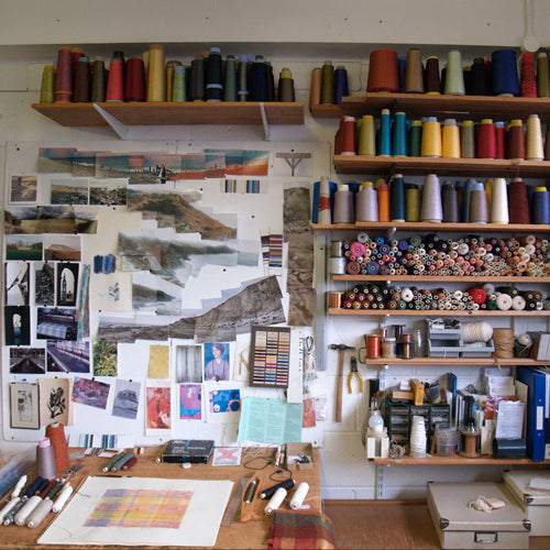 Image of Charlotte Grierson's studio showing her inspiration board full of image over her drawing board, and shelves stocked with colourful yarns.