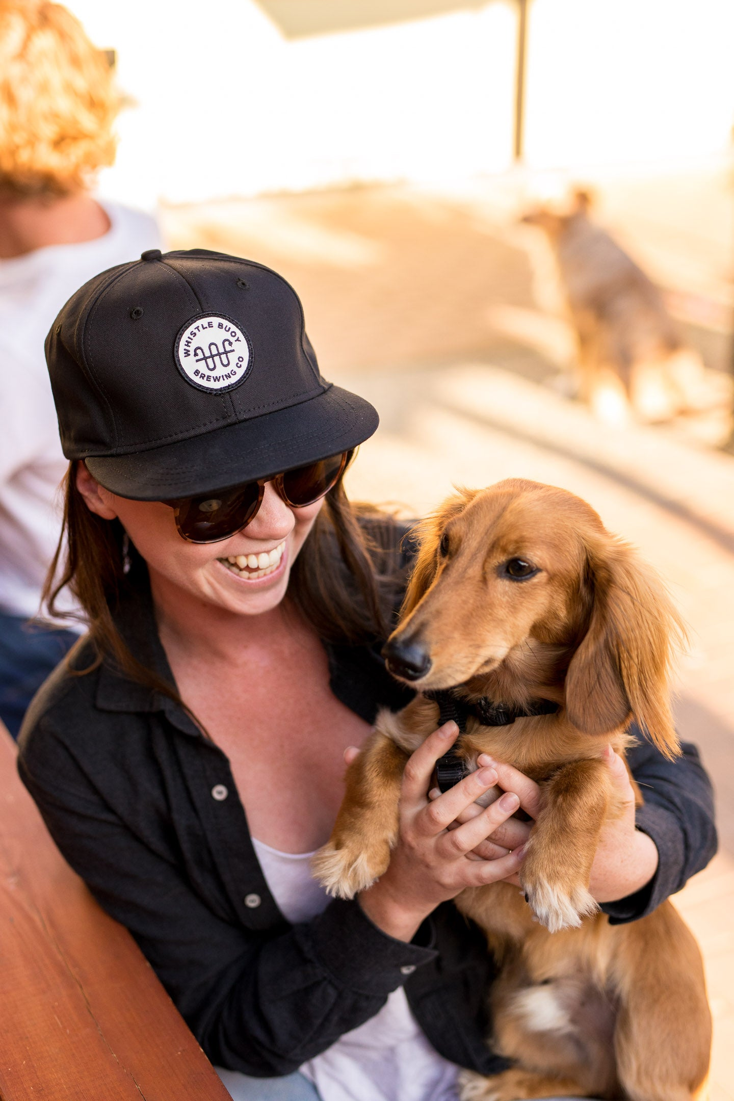 Whistle Buoy Game Cap worn by woman holding dog