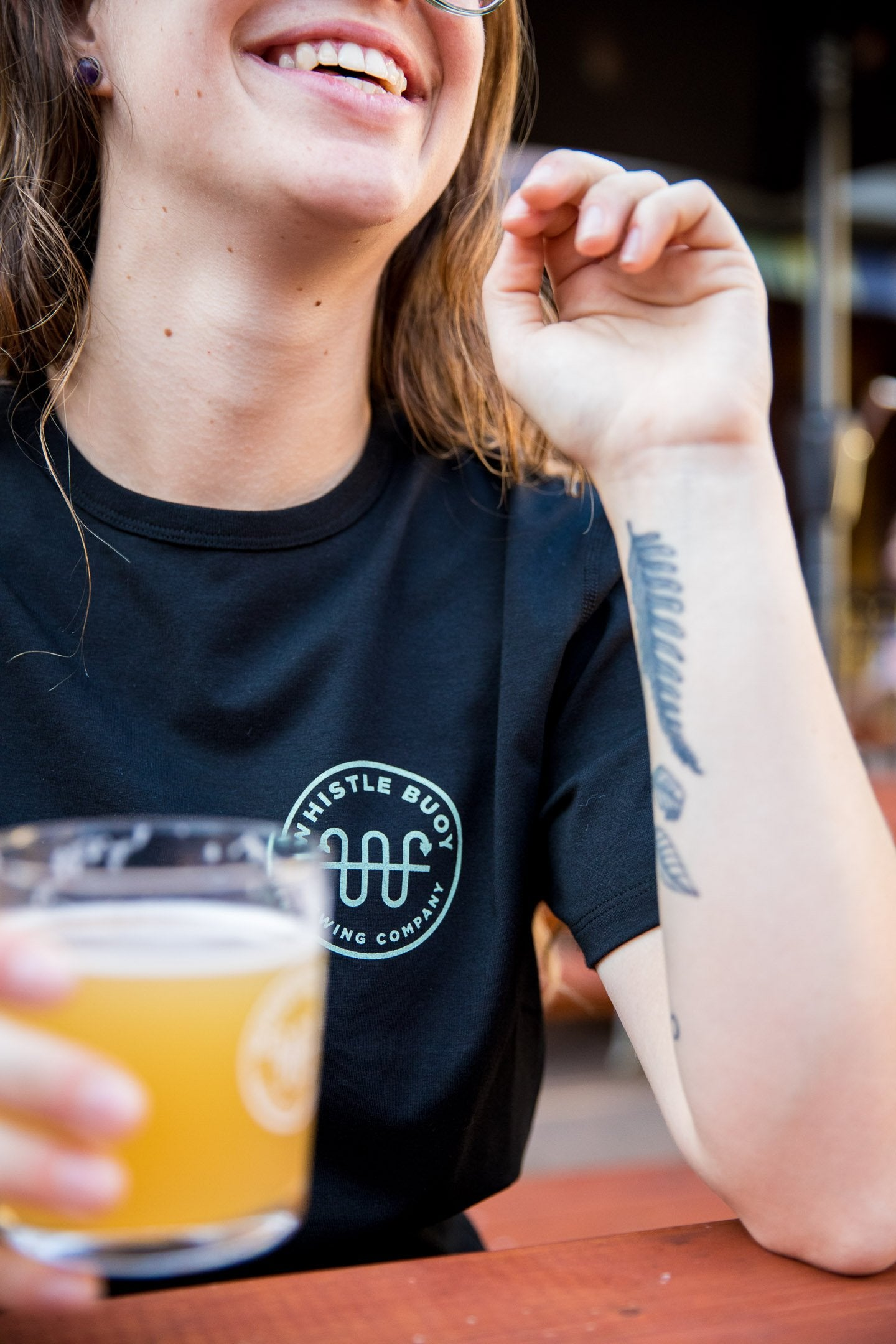 Women wearing black Whistle Buoy emblem t-shirt on patio