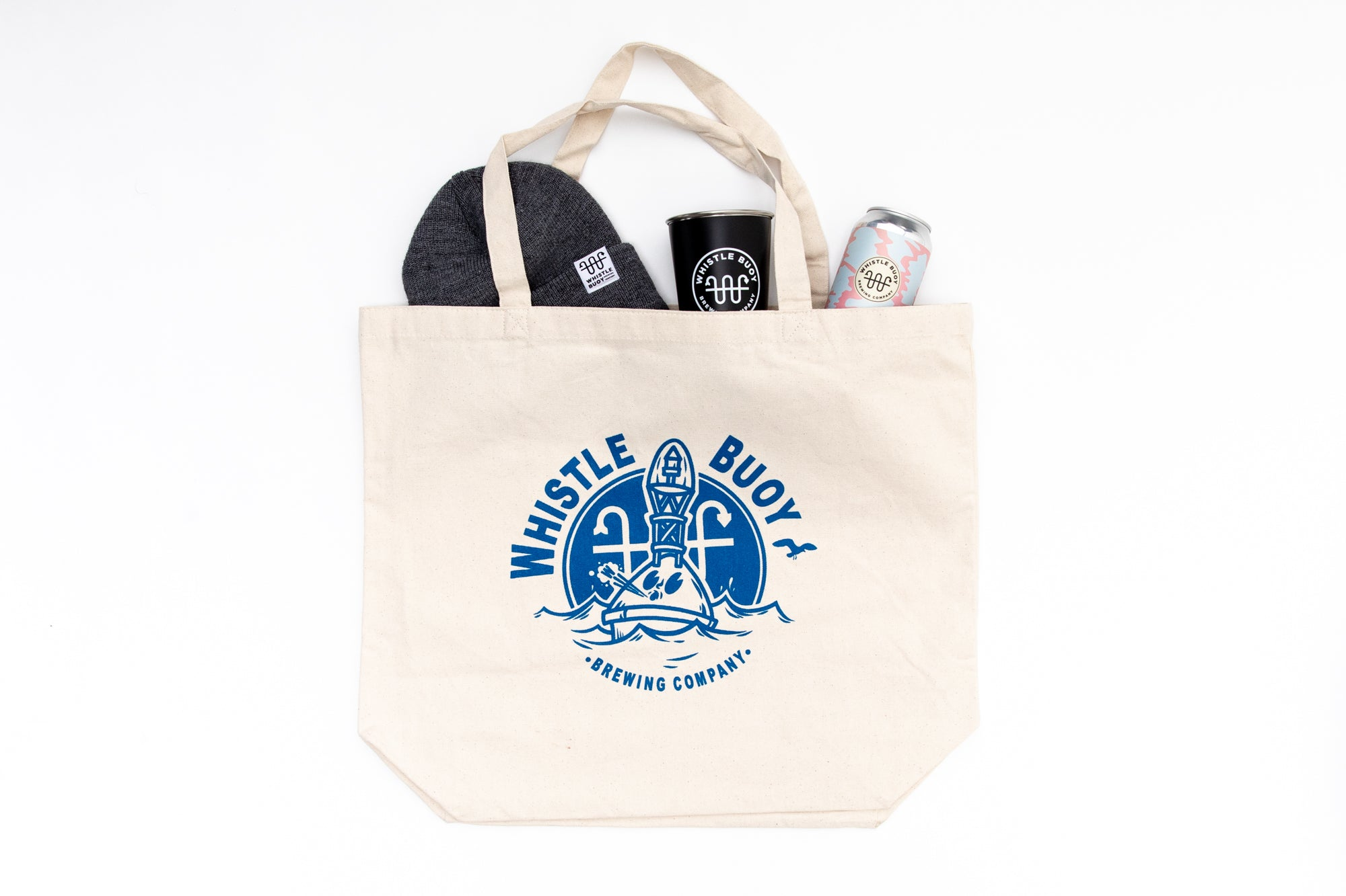 White Whistle Buoy tote bag with blue logo with products spilling out - studio shot