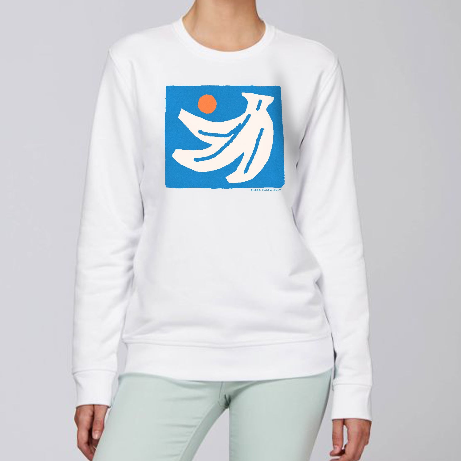 Photo of a model wearing a white sweater. The print on the sweater is an off-white hand of bananas with an orange circle next to them on a blue square background.