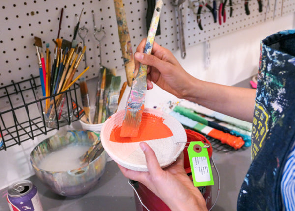 Image of a jewelry tray being painted by hand.