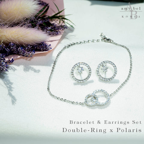 A reference cut of Korean fashion bracelet Double Ring in Silver Rhodium color and Stud earrings Polaris in Silver Rhodium color in the white background with the plant.