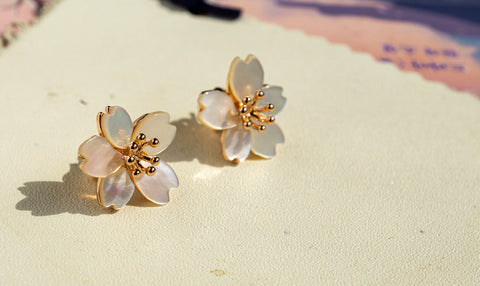 A set of Korean handmade earrings Cherry Bloom is placed on a piece of leather in the sunshine.