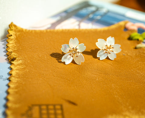 A set of Korean handmade earrings Cherry Bloom is showing its front side in the sunshine.
