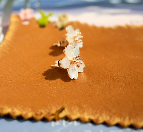 A set of Korean handmade earrings Cherry Bloom is showing its 90 degree side in the sunshine.