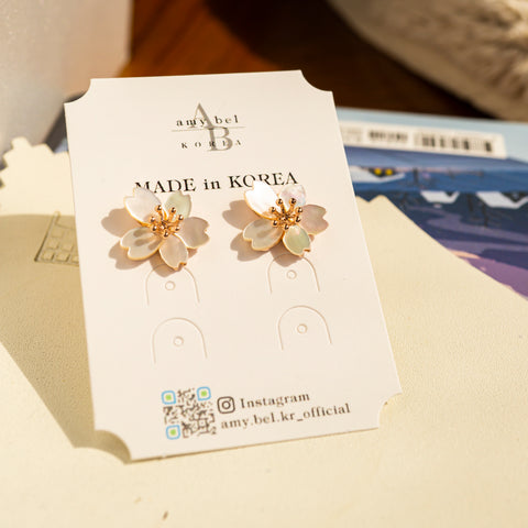 A set of Korean handmade earrings Cherry Bloom is placed on amy bel Korea accessory tag in the sunshine.