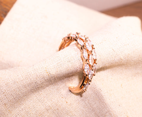 A piece of Korea Earrings Cubic shower in 14KGP Rose Gold is placed on a white piece of cloth.
