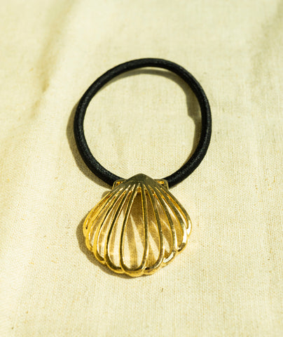 amy bel Korea hair accessory Hair tie band I (Shell Frame) in Gold color is placed in the sunlight.