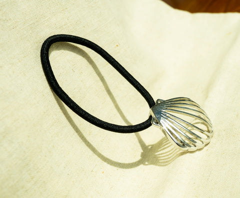 amy bel Korea hair accessory Hair tie band I (Shell Frame) in Silver color is placed in the sunlight.