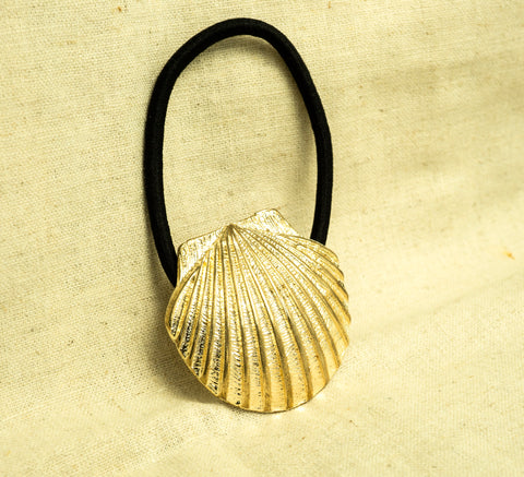 amy bel Korea hair accessory Hair tie band II (Whole Shell) in Gold color is placed in the sunlight.