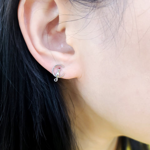 A piece of Korean earrings Loona Kitty 925 Silver in Silver color is worn by a model..