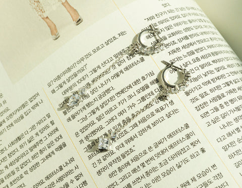 A set of Korean earrings Loona Tail is placed on the korean magazine.