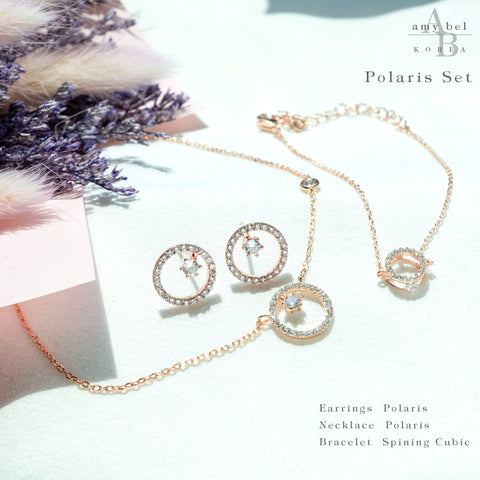 A wide set of Korean Jewelry Polaris earrings, necklace, and spining cubic bracelet is placed on the white piece of cloth with some plants.