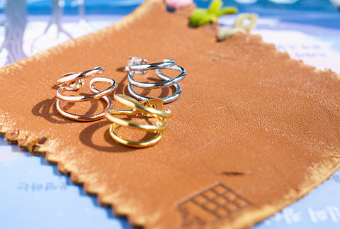 Korean earrings Spiral Little Hoop in Gold, Silver, and Rose Gold are placed on the leather piece in sunshine.