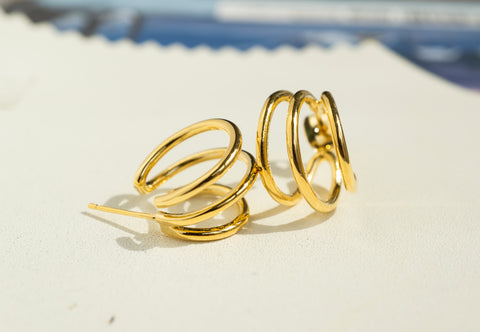 A set of Korean earrings Spiral Little Hoop in Gold color is placed on the white leather piece..