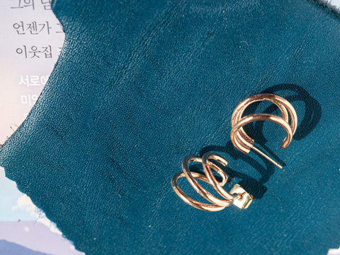 A set of Korean earrings Spiral Little Hoop in Rose Gold color is placed on the leather piece.