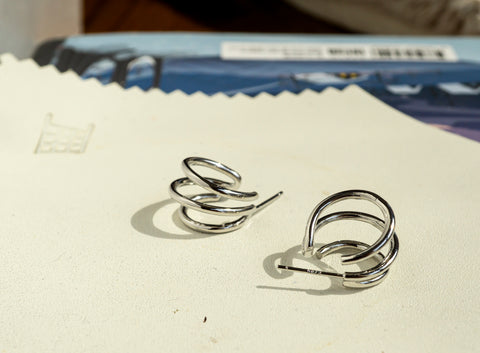 A set of Korean earrings Spiral Little Hoop in Silver color is placed on the white leather piece.