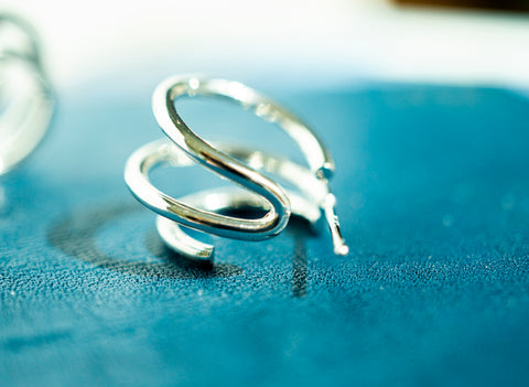 A piece of Korean earrings Spiral Little Hoop in Silver color shows its detail.