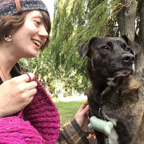 Photo of Joining Yarns owner who is knitting and smiling at her dog.