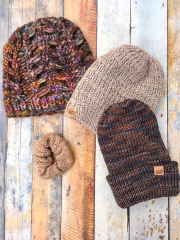 Three brown hats arranged in an arch with a brown scrunchy below the arch