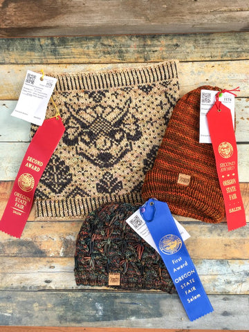 Beige cowl with black colorwork triceratops winning a second place ribbon, orange folded brim hat with a second place ribbon, and multicolor blue/green hat with a blue ribbon arranged on a wooden background