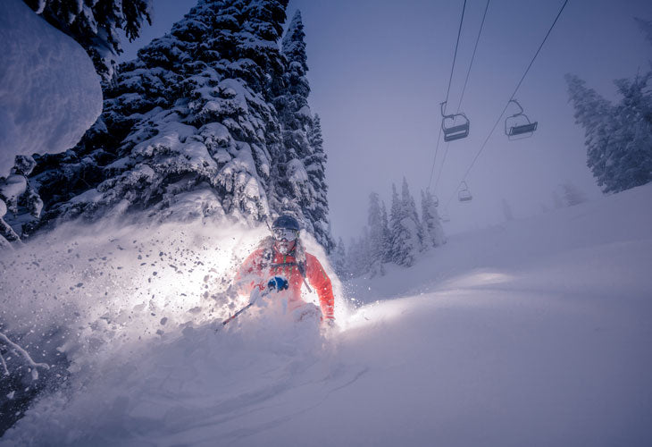 skier at big white slashing pow