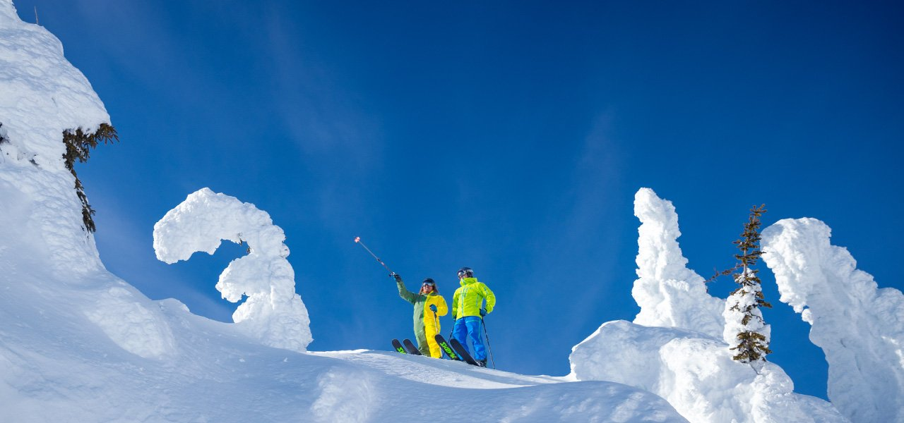 Skiers overlooking terrain with Skevik bases overhanging face