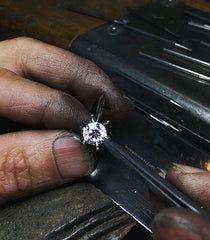 A jeweller setting a round brilliant cut diamond into an engagement ring