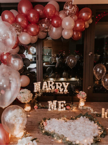 lavish proposal set up in an apartment with balloons and a marry me sign displayed