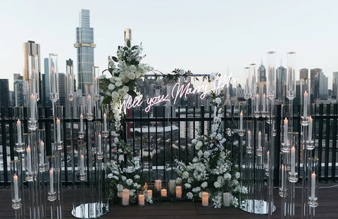 Rooftop view of the Melbourne city skyline with a lovely floral proposal arrangement and a marry me sign displayed with candles surrounding