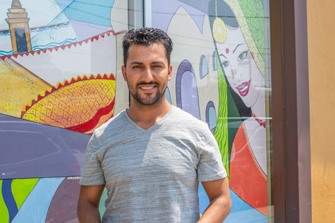 Man smiling at the camera and standing in front of a mural