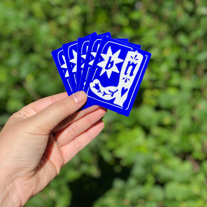 pictured is a hand holding 5 blue and white stickers. on the stickers is a boot and a star, with the letters 'b' and 'n' on each item.