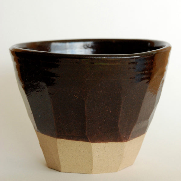 Hand thrown stoneware cup, subtly finished with an irregular cut surface. Decorated in a glossy bark brown Tenmoko glaze with a contrasting buff-coloured foot.