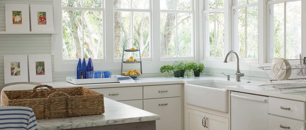 kitchen with big windows, white cabinetry and an island with whicker tray on top