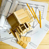 wooden house model on top of floor plan papers