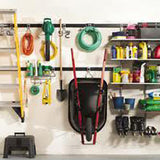 ladder hoses wheel barrow and other outdoor equipment hanging on wall