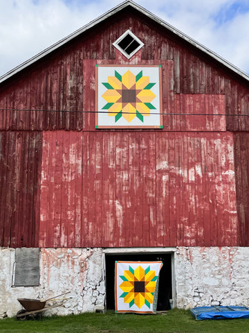 Scenic Road quilt in front of barn