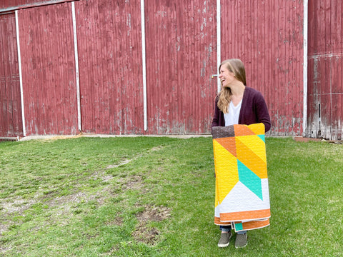 amanda in front of barn holding quilt
