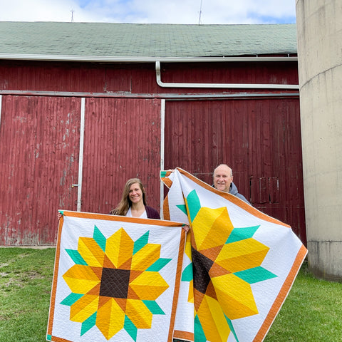 Amanda and Pat in front of barn holding Scenic Road quilts