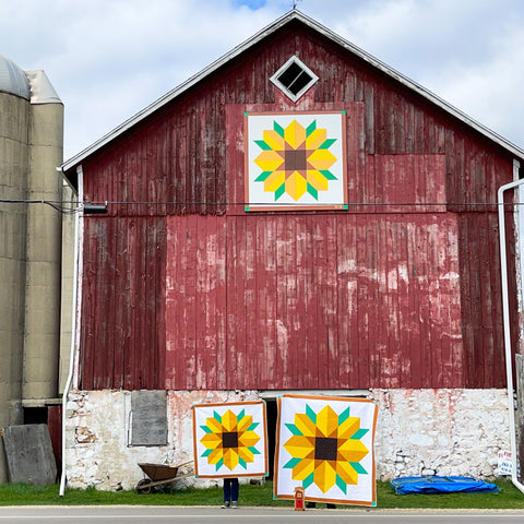 two quilts in front of barn