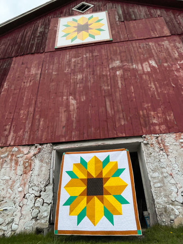 Photo of scenic road quilt in front of barn with barn quilt